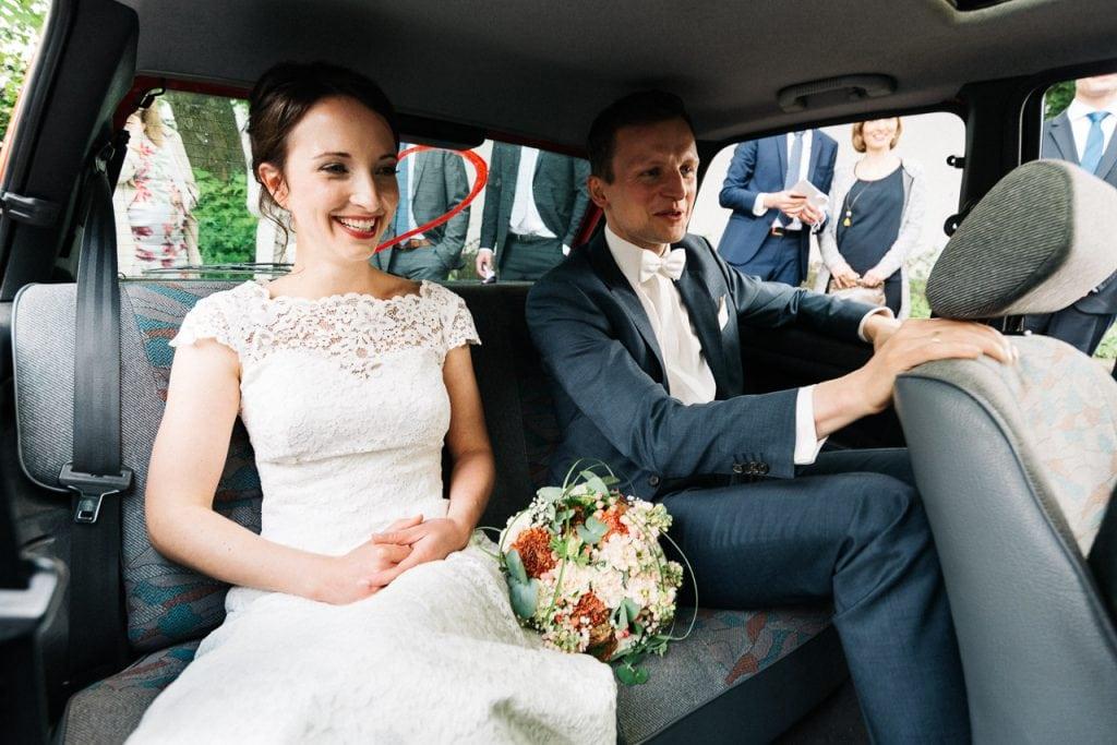Braut und Bräutigam im Hochzeitsauto.
