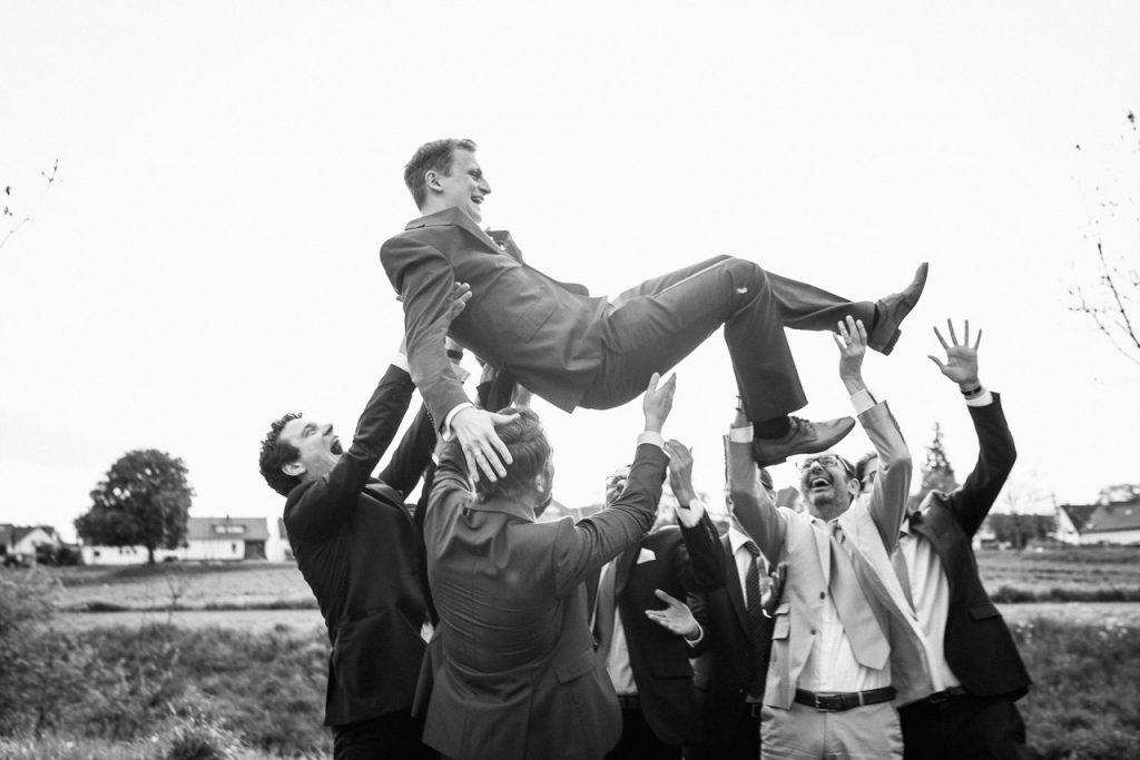 Der Bräutigam wird hochgeworfen.