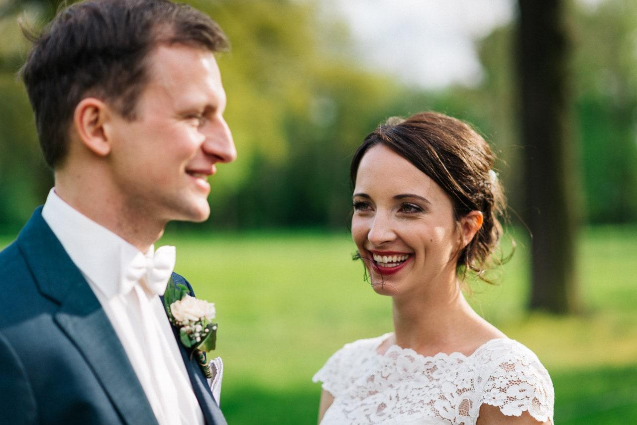 Die Braut strahlt ihren Bräutigam an.