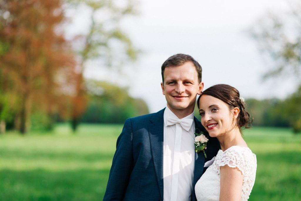 Portrait vom Brautpaar auf einer grünen Wiese.