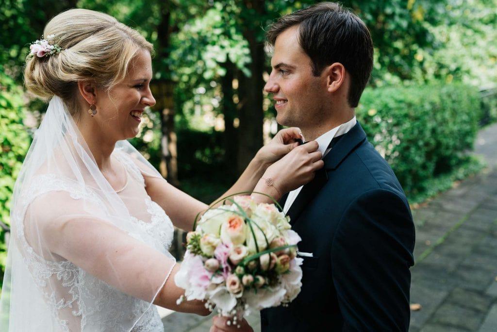 Die Braut richtet die Fliege des Bräutigams.