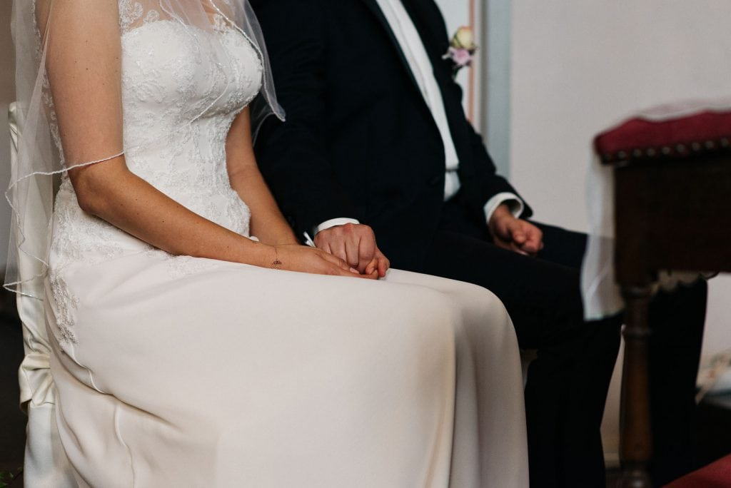 Das Brautpaar hält Händchen.