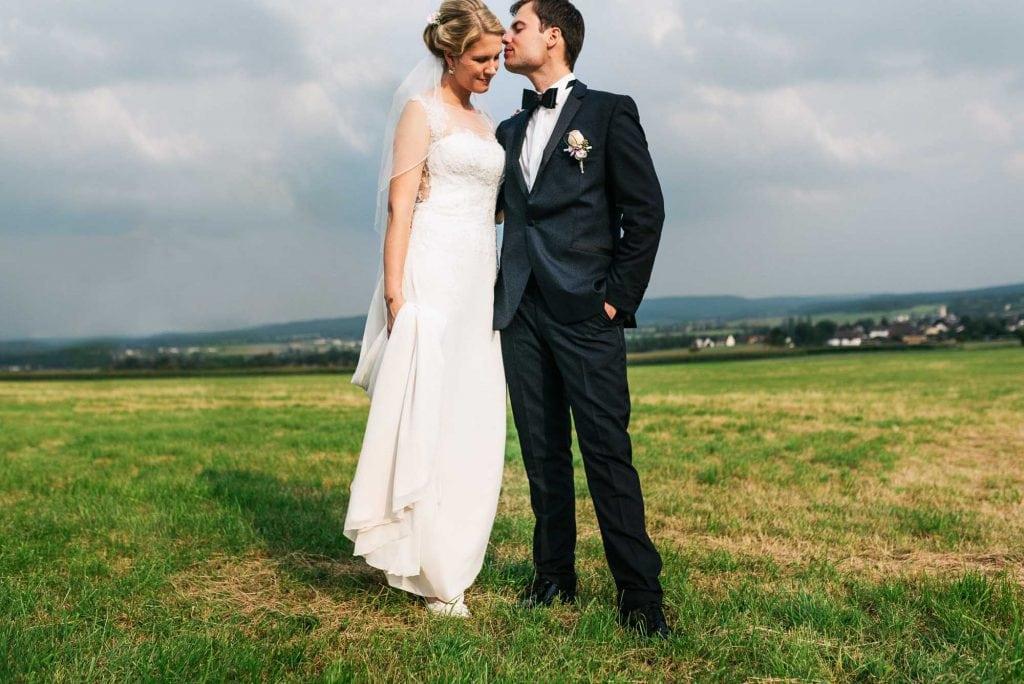 Der Bräutigam küsst die Braut auf den Kopf.