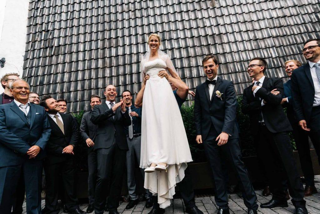 Gruppenbild auf dem die Braut angehoben wird.