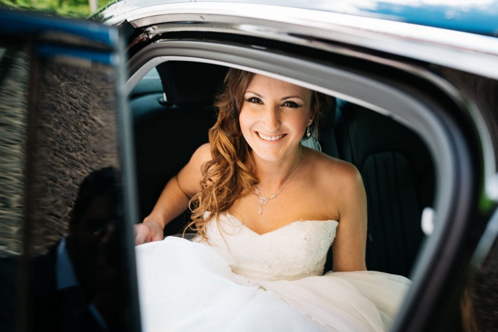 Die Braut schaut durch die offene Autotür.