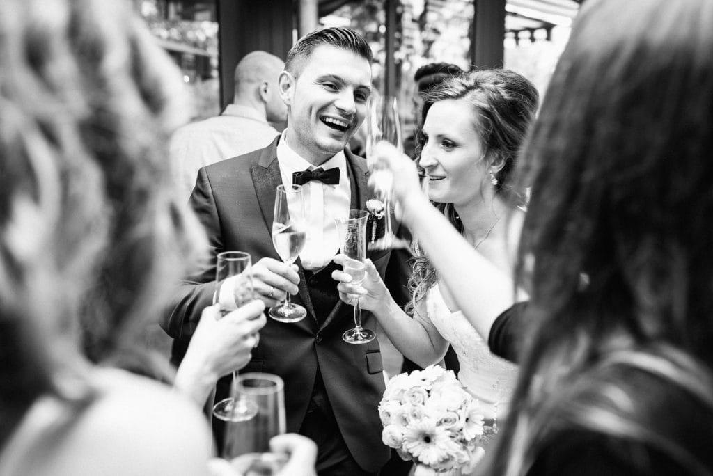 Braut und Bräutigam stoßen miteinander an.