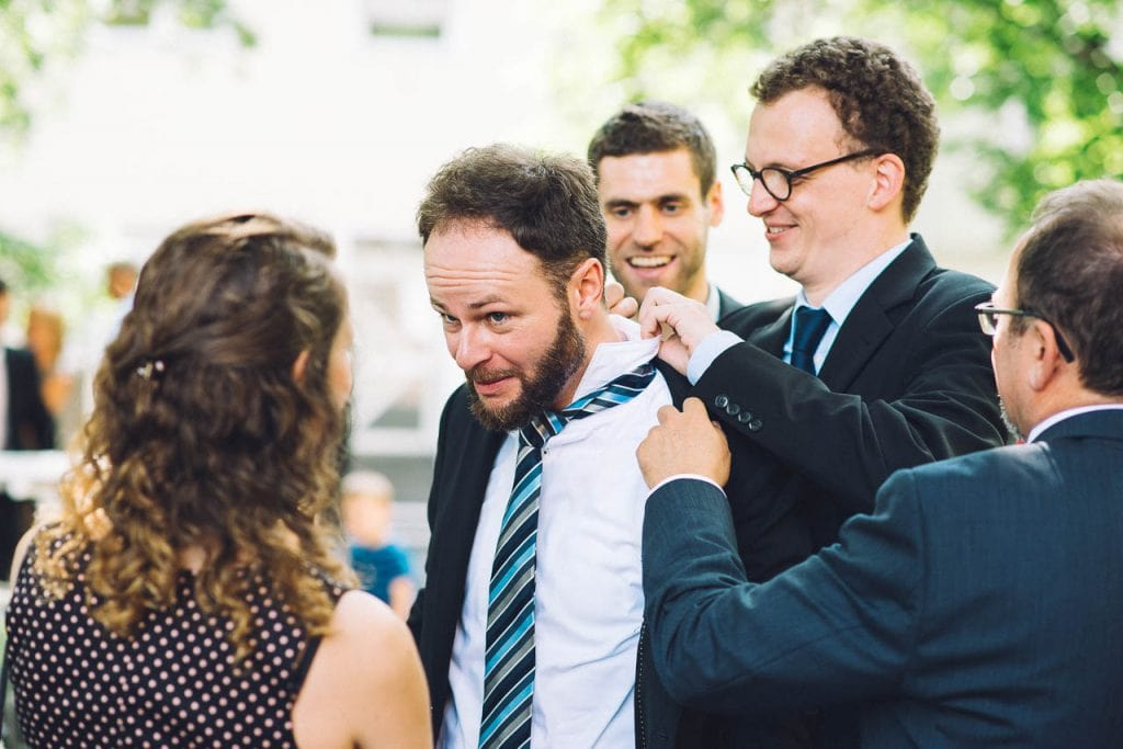 Ein Hochzeitsgast bekommt Hilfe mit seiner Krawatte.