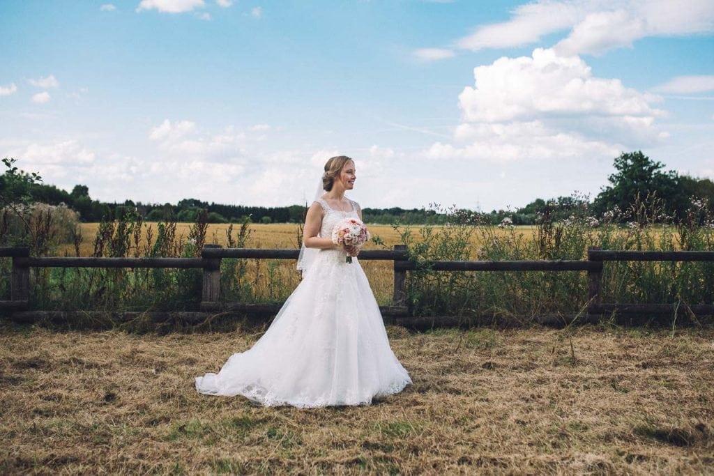 Portrait der Braut vor einem Feld.