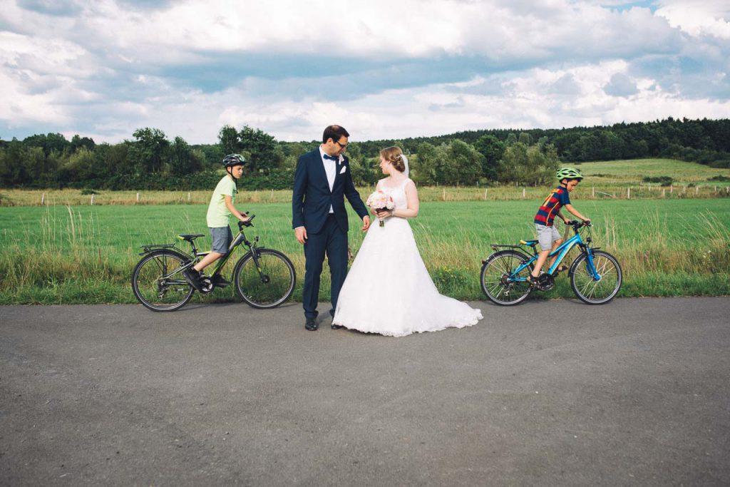 Radfahrende Kinder neben dem Brautpaar.