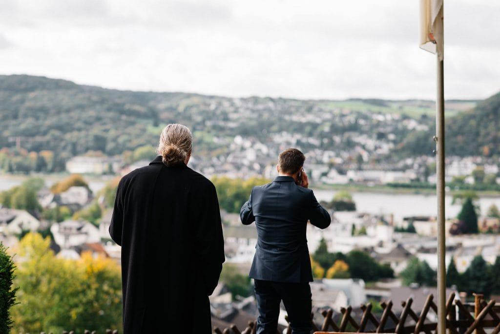 Der Bräutigam schaut auf den Rhein und telefoniert.