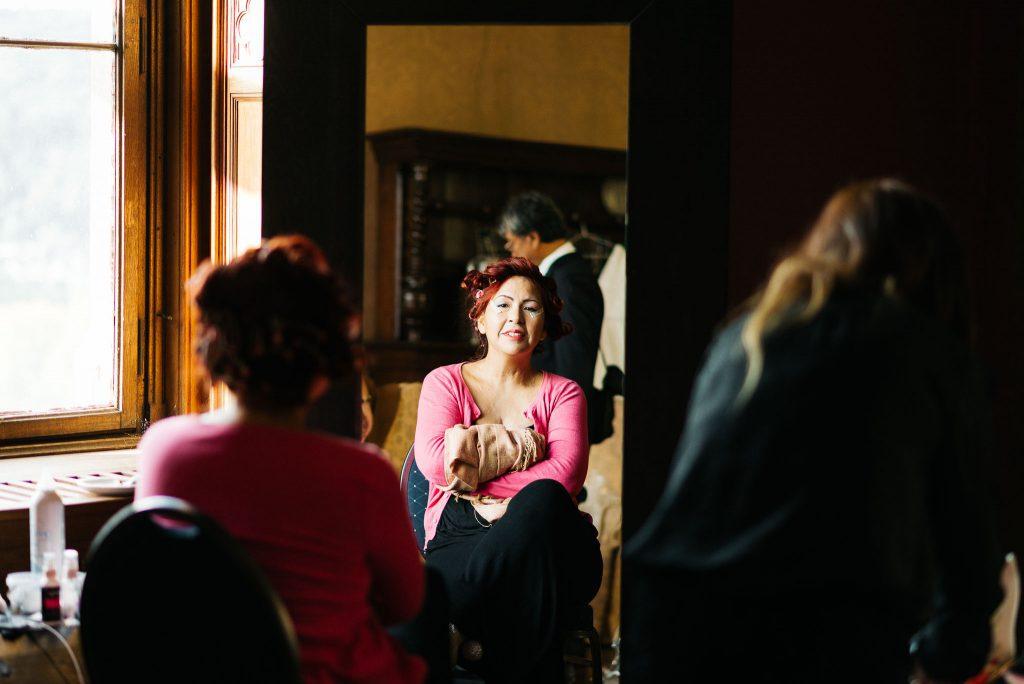 Die Braut betrachtet sich im Spiegel.