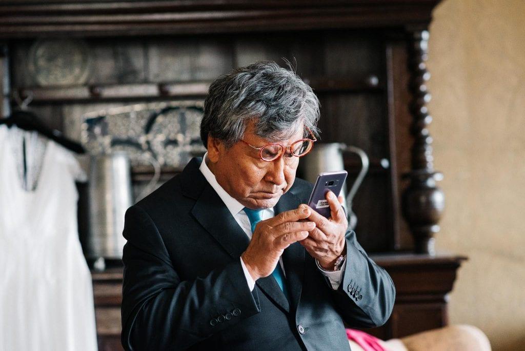 Der Brautvater ließt eine Textnachricht.