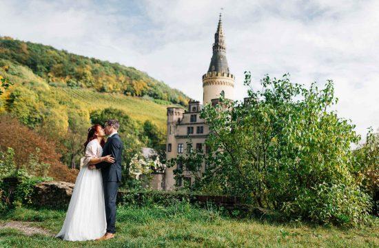 Panorama von Schloss Arenfels mit dem Brautpaar davor.