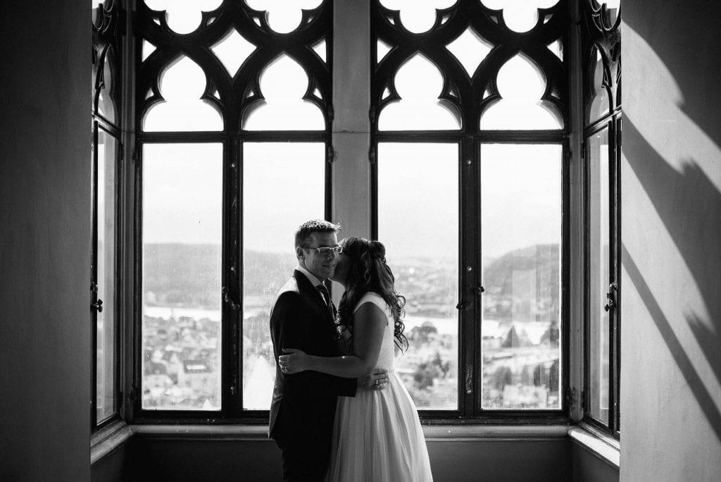 Das Brautpaar im Schloss vor einem Fenster.