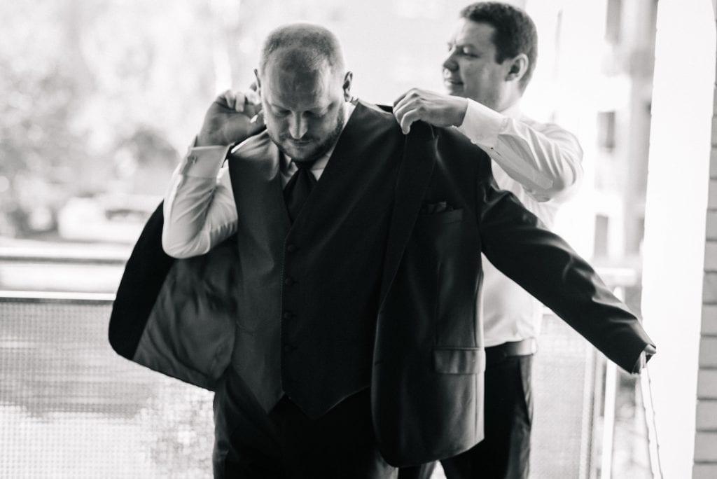 Der Bräutigam zieht sein Jackett an.