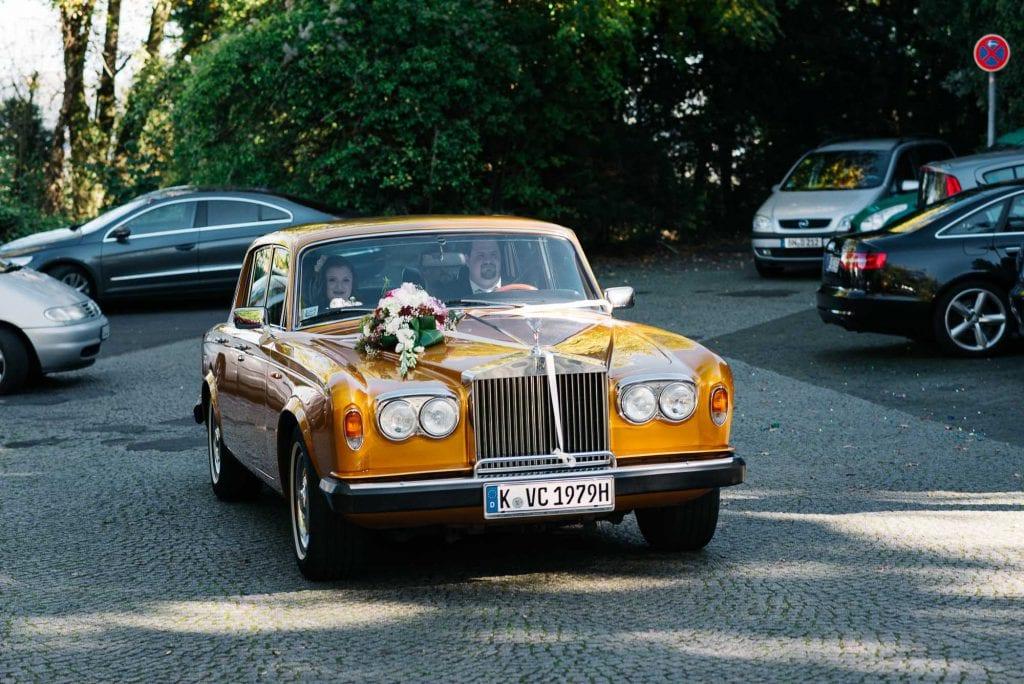Das Hochzeitsauto mit der Braut fährt ein.