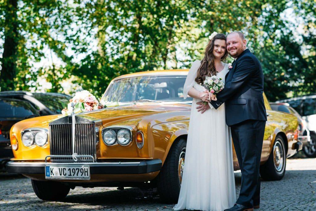 Braut und Bräutigam vor dem Hochzeitsauto.
