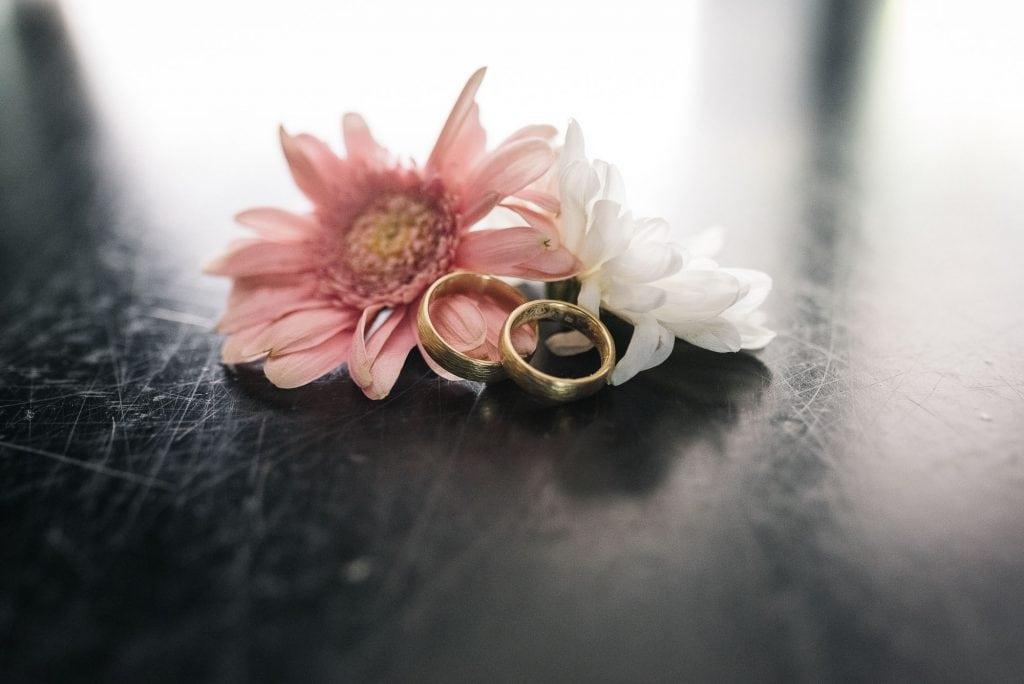Die Eheringe an einer Blume.