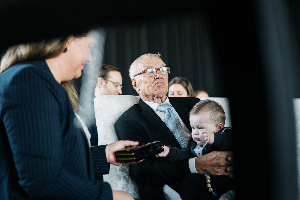 Hochzeitsgast mit Kind im Arm.