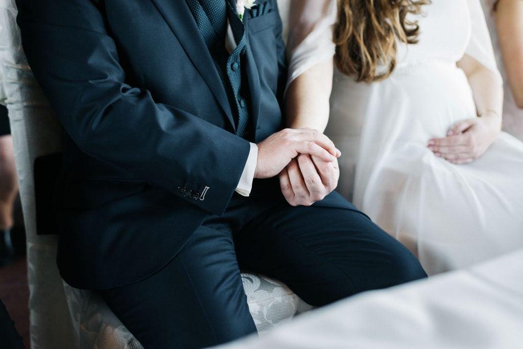Braut und Bräutigam halten Händchen.