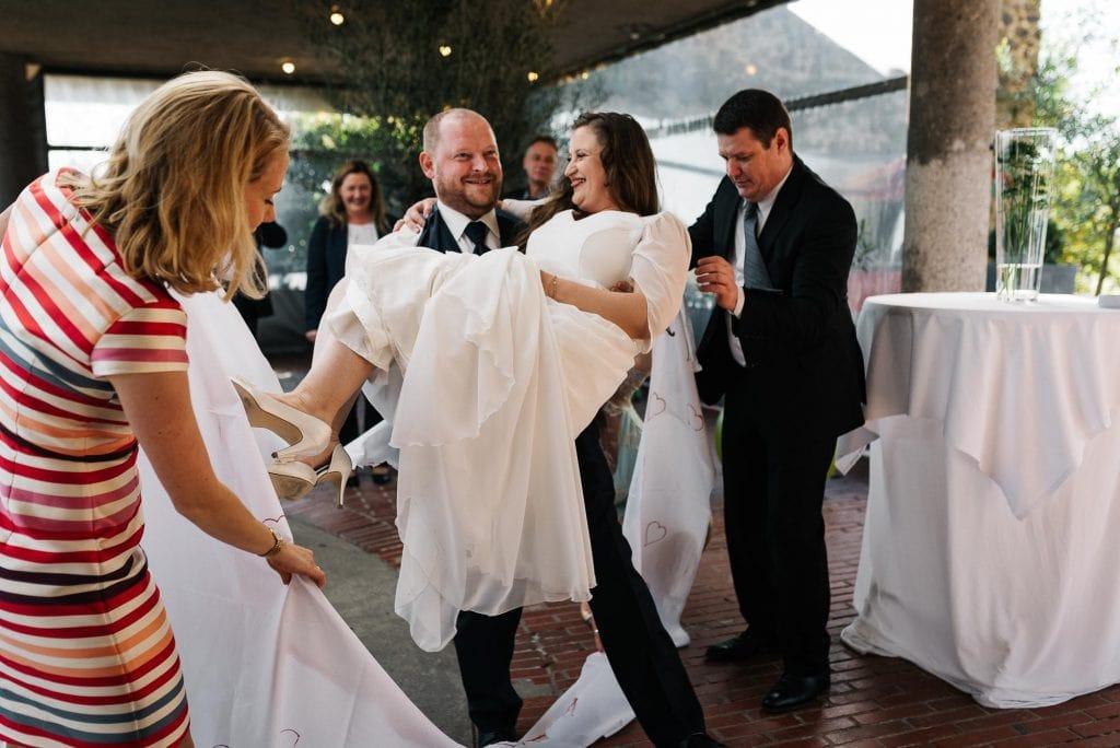Der Bräutigam trägt die Braut.