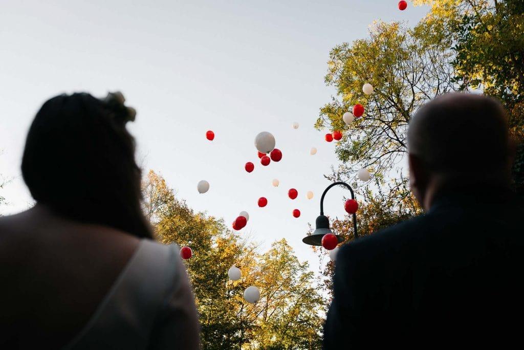 Das Brautpaar schaut Ballons hinterher.