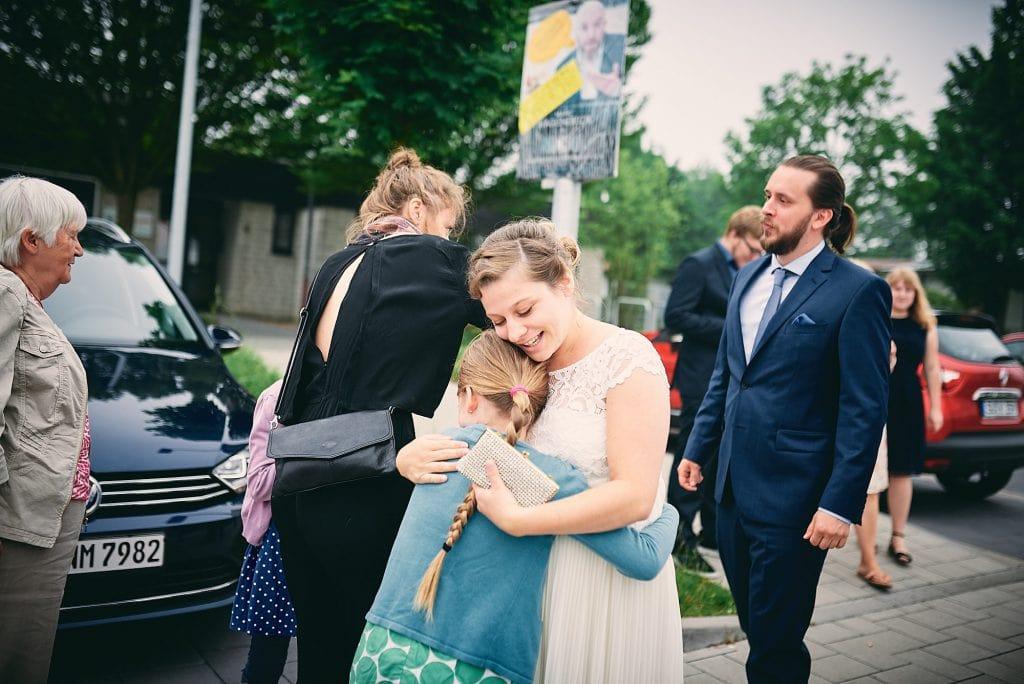 Die Braut umarmt die ankommenden Hochzeitsgäste.