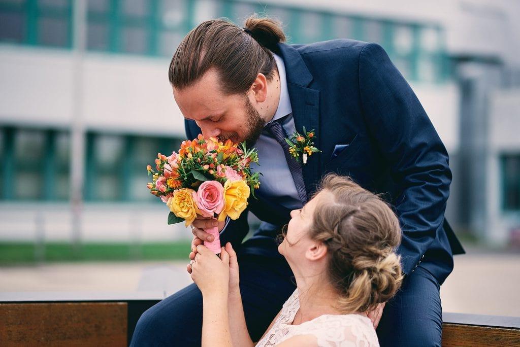 Der Bräutigam riecht am Brautstrauß.