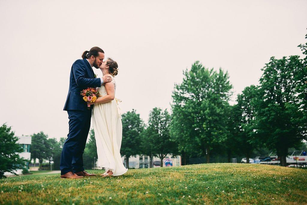 Das Brautpaar küsst sich auf der Hügelkuppe.
