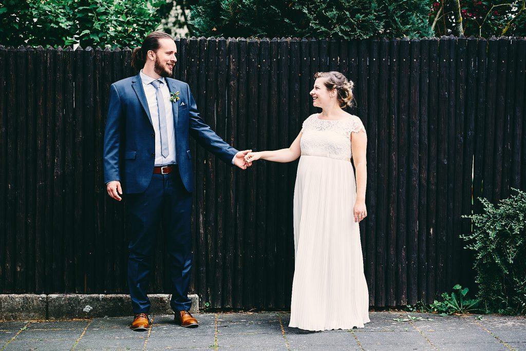 Das Brautpaar vor einer Holzwand.