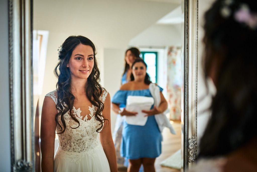 Die Braut betrachtet sich selbst im Spiegel.