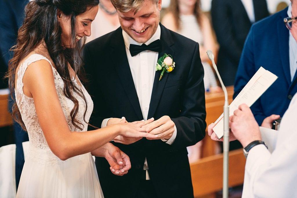 Braut und Bräutigam stecken sich die Ringe an.