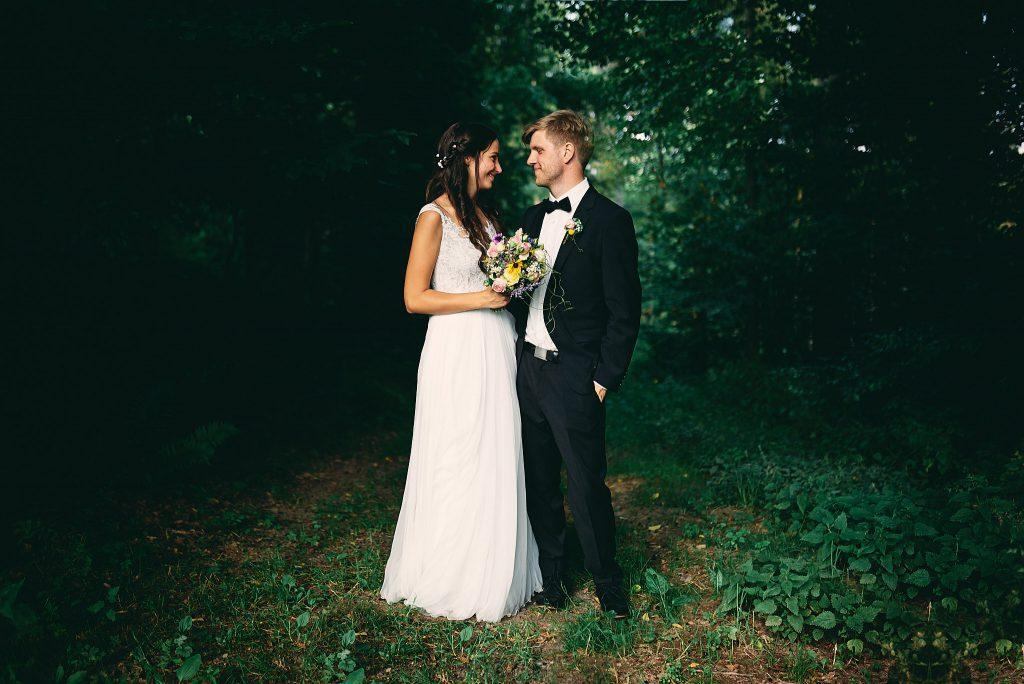 Braut und Bräutigam stehen im Wald.