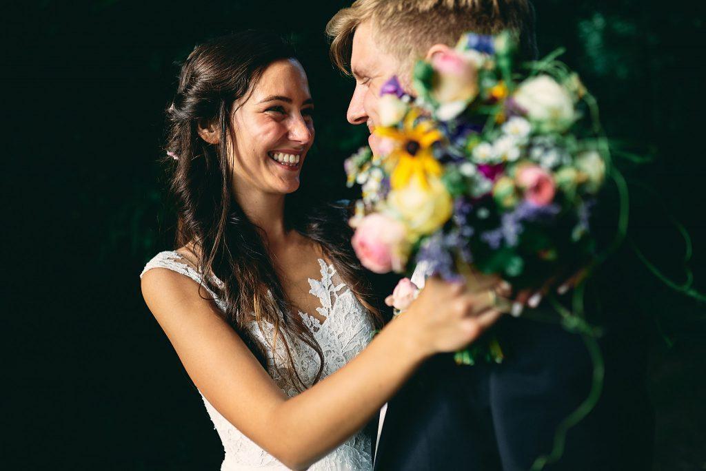 Die Braut lacht den Bräutigam an.