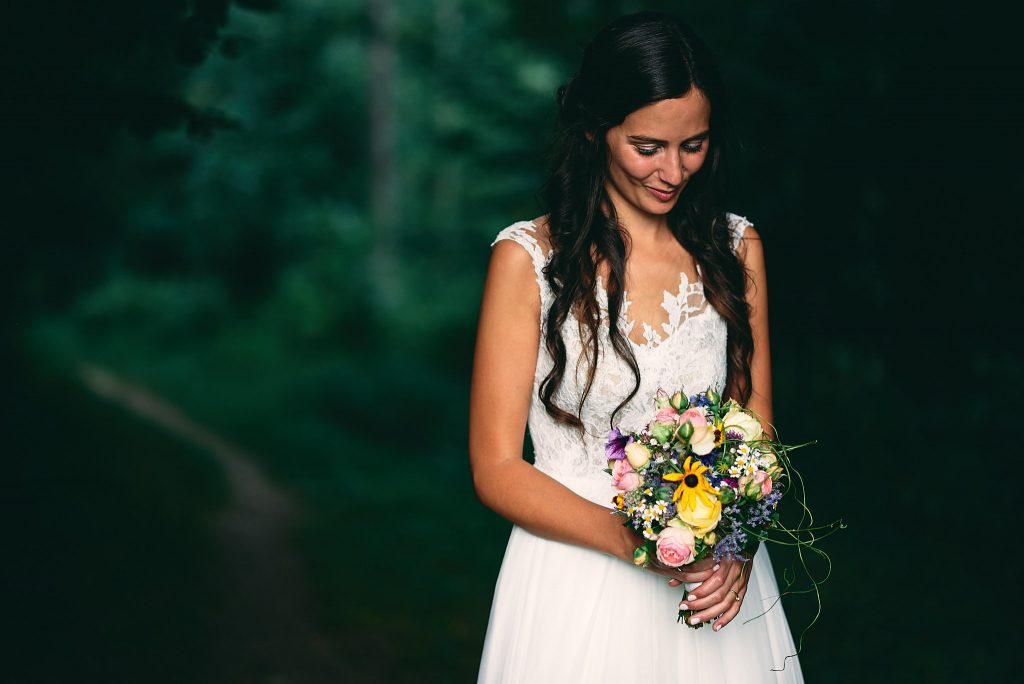 Die braut schaut an sich herab auf den Brautstrauß.
