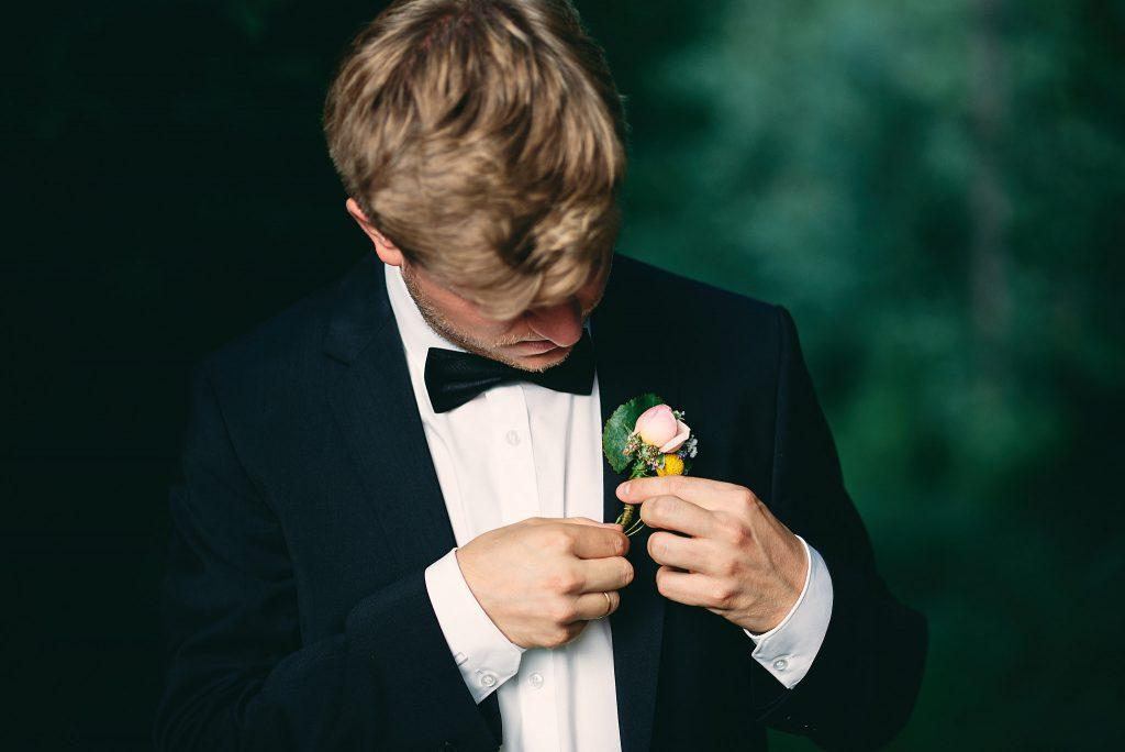 Der Bräutigam richtet seine Ansteckblume.