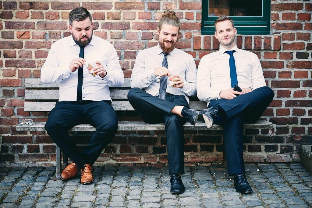 Drei Hochzeitsgäste auf einer Bank.