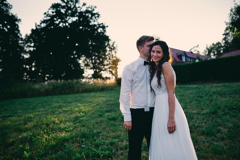 Der Bräutigam küsst die Braut auf den Kopf im Sonnenuntergang.