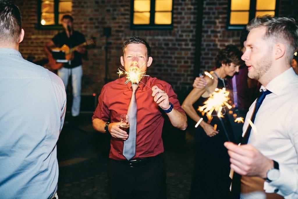 Ein Hochzeitsgast mit einer Wunderkerze.