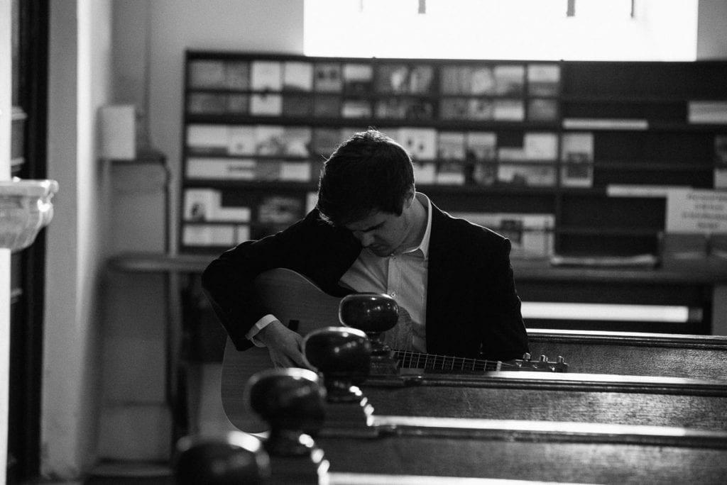 Ein Musiker stimmt seine Gitarre.