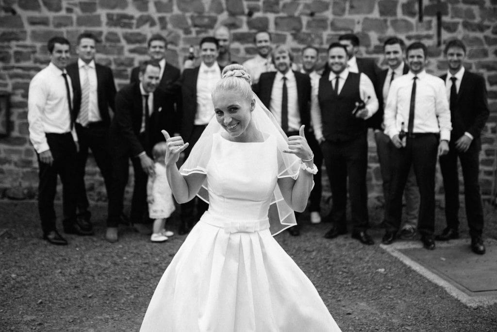 Die Braut vor einer Gruppe von Hochzeitsgästen.