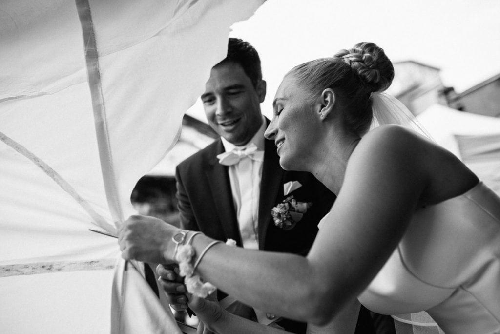 Braut und Bräutigam zerschneiden ein Tuch.
