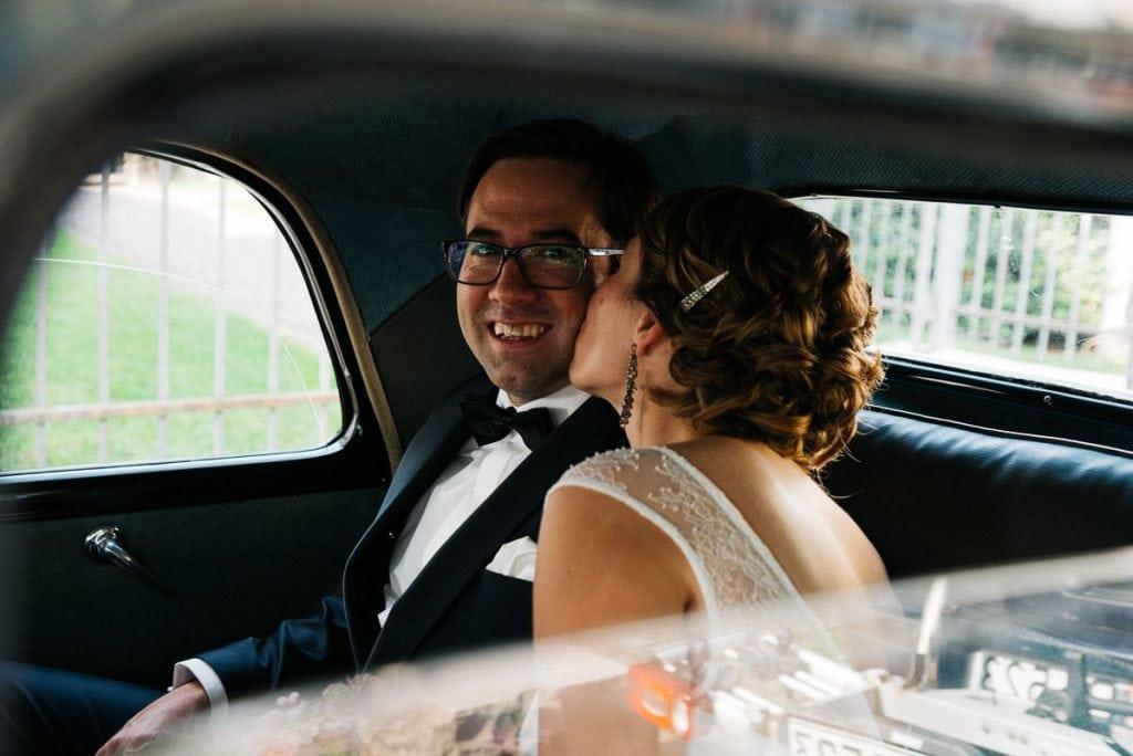 Die Braut küsst den Bräutigam im Hochzeitsauto.