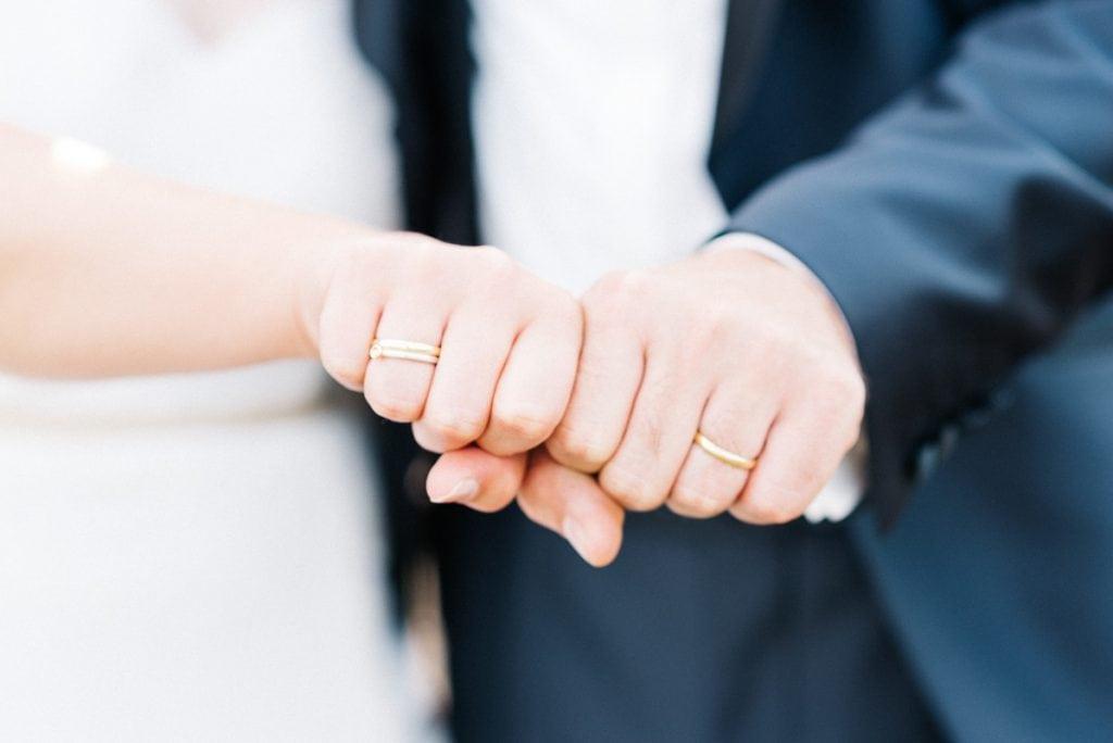 Das Brautpaar zeigt seine Ringe.