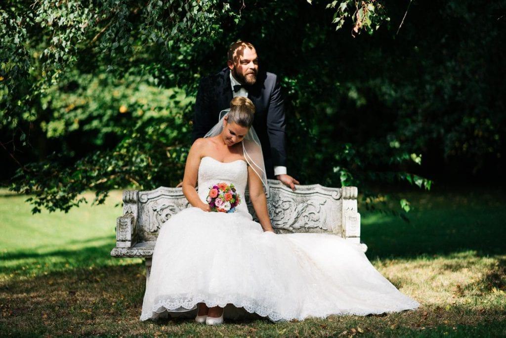 Das Brautpaar auf einer Bank im Park.