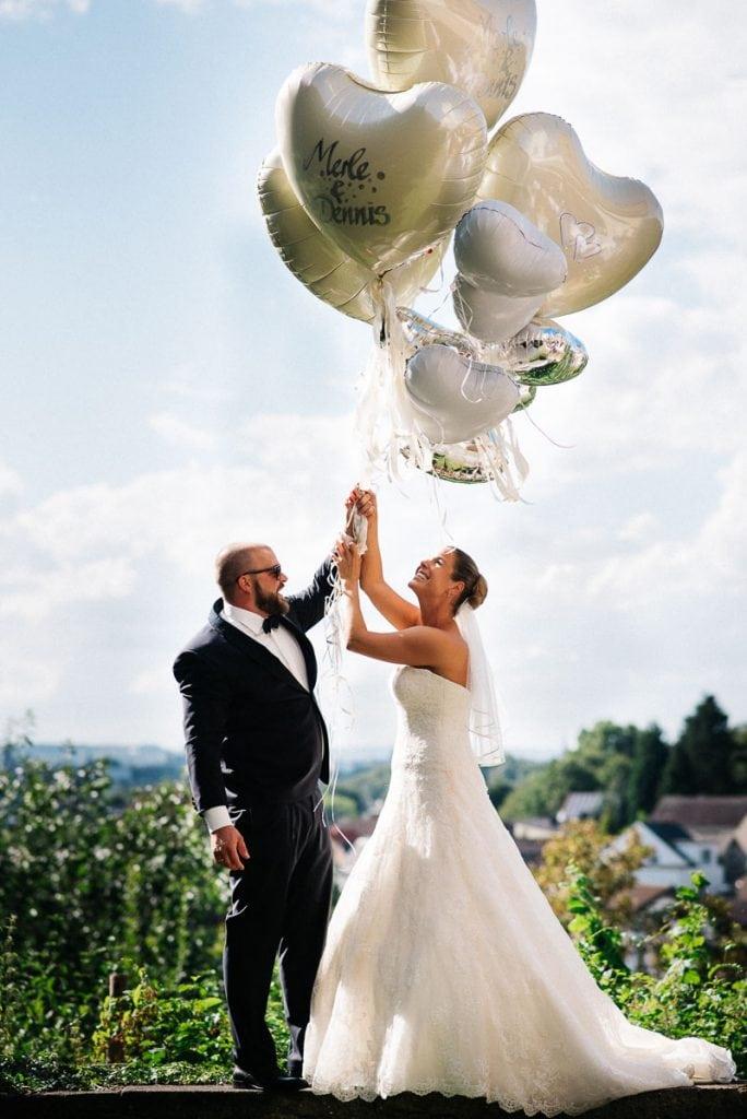 Braut und Brautpaar halten Ballons fest.