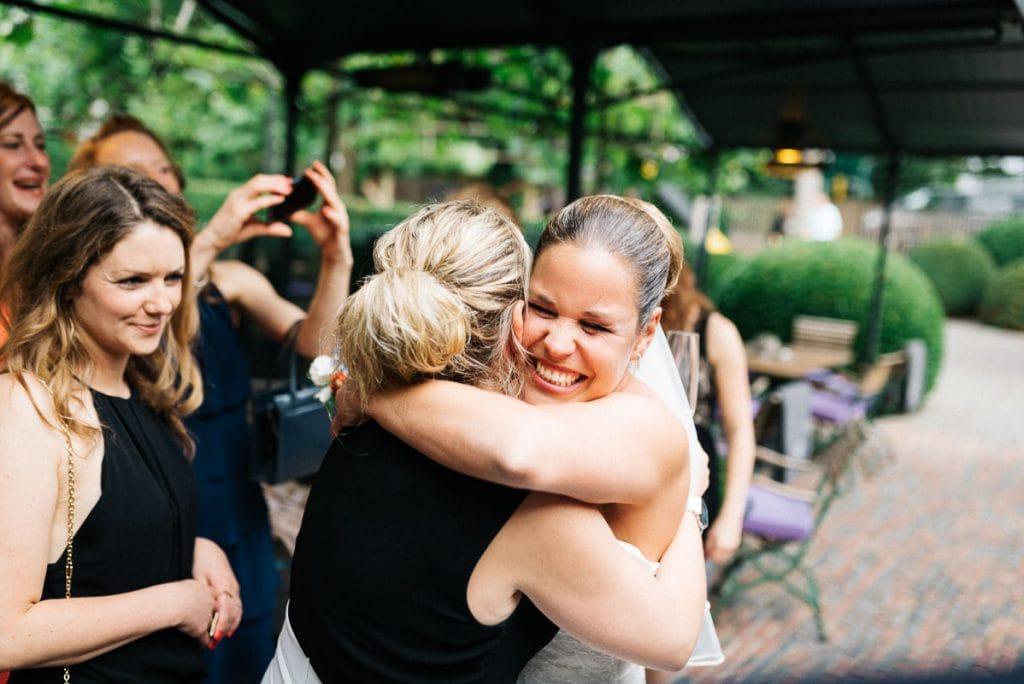 Die Braut umarmt einen Gast.