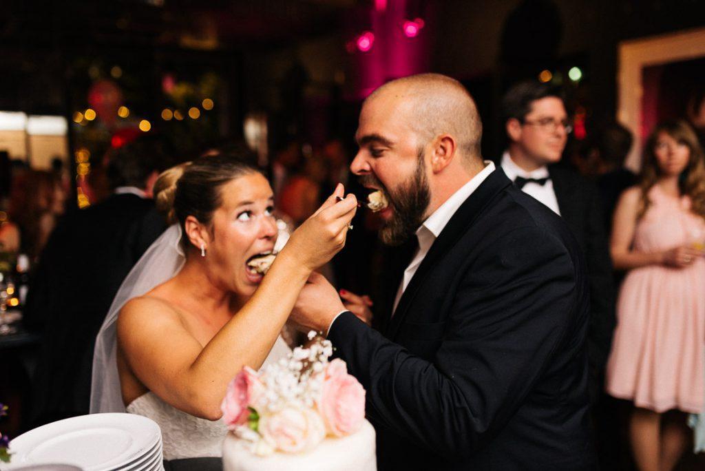 Das Brautpaar füttert sich mit Torte.
