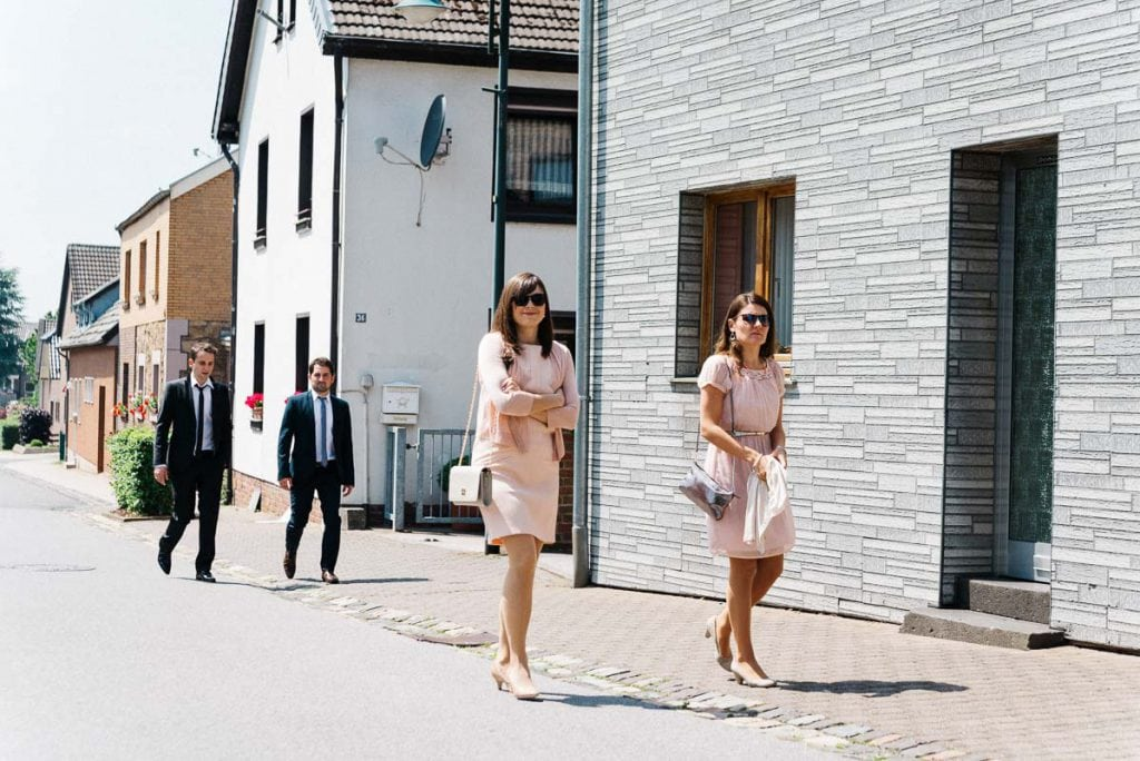 Hochzeitsgäste kommen an der Kirche an.