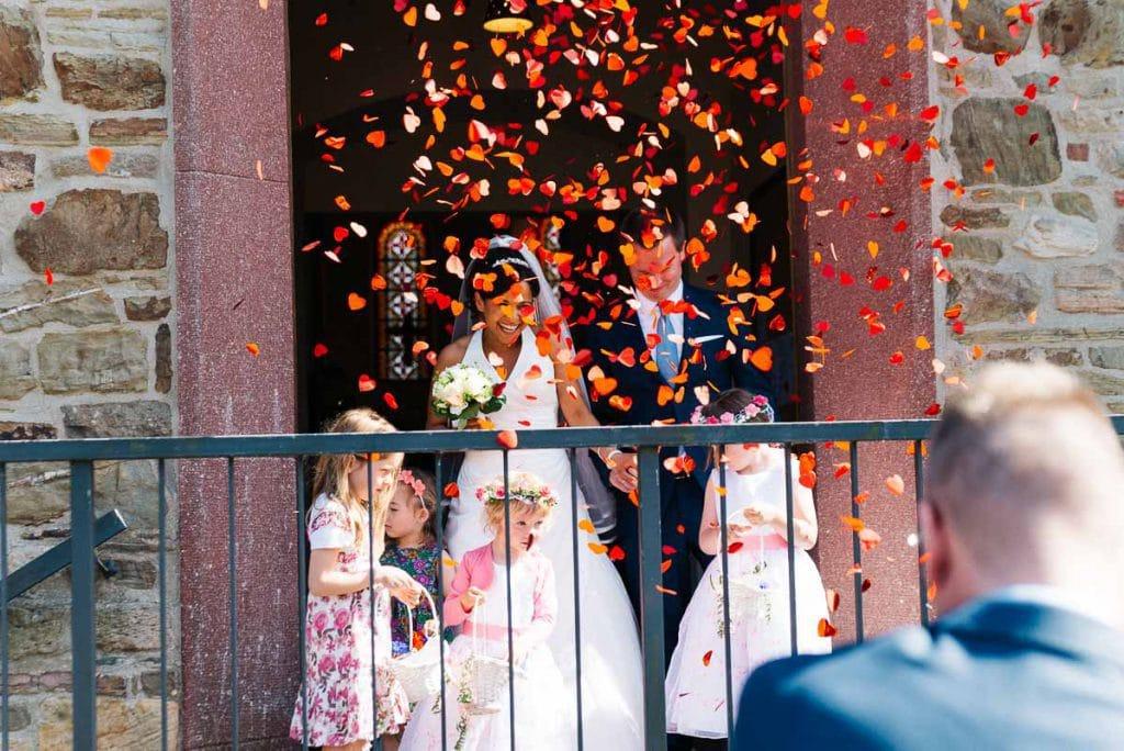Das Brautpaar im Konfettiregen.